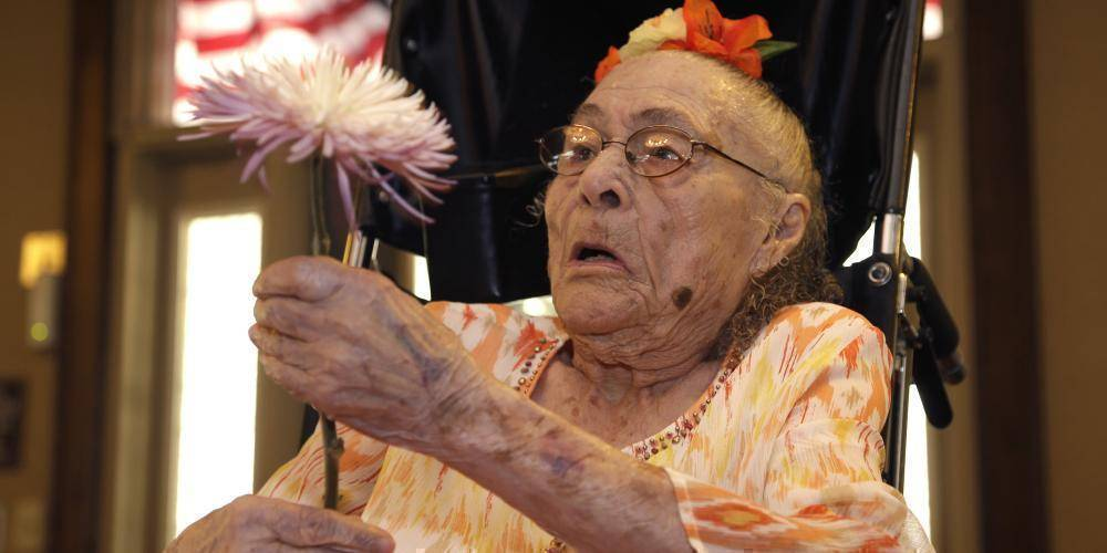 Gertrude Weaver holds a flower given to her a day before her 116th birthday, at Silver Oaks Health and Rehabilitation Center in Camden, Ark., Thursday, July 3, 2014. The Gerontology Research Group says Weaver is the oldest person in the United States and second-oldest person in the world. (AP Photo/Danny Johnston)